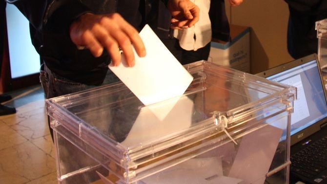 Un votant introduint el vot en una urna