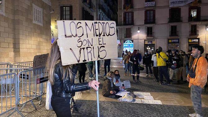 Una manifestant negacionista de la Covid sosté un cartell contra els mitjans