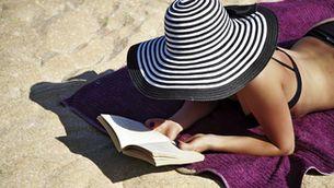 Dona llegint a la platja, protegint-se del sol amb un barret de ratlles.
