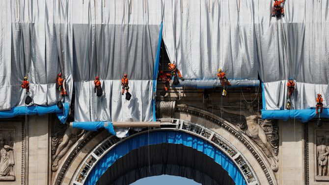 Uns operaris es despengen per l'Arc de Triomf per desplegar la tela