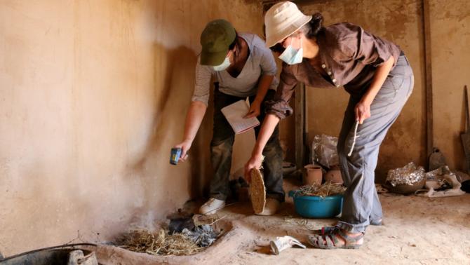 Dues investigadores de l'ICAC analitzant una llar de foc recreada a la Ciutadella Ibèrica de Calafell